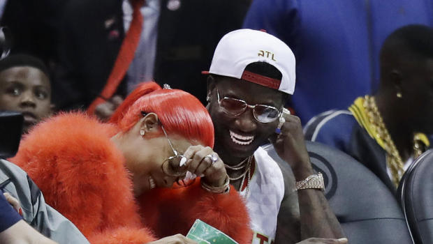 Hip Hop artist Gucci Mane, right, laughs with Keyshia Ka'oir after he proposed to her in the fourth quarter of an NBA basketball game between the Atlanta Hawks and the New Orleans Pelicans in Atlanta, Tuesday, Nov. 22, 2016. (AP Photo/David Goldman)