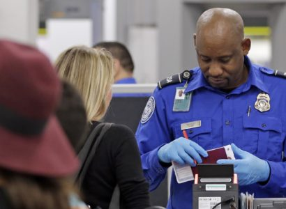 In this photo taken Thursday, June 30, 2016, a Transportation Security Administration agent checks traveling documents of a passenger at Miami International Airport in Miami. (AP Photo/Alan Diaz)