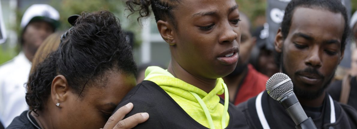 Monika Williams, center, stands with her brother Domico Jones, right, as she talks about their sister, Charleena Lyles, at a vigil outside where Lyles was shot and killed Sunday by police, Tuesday, June 20, 2017 in Seattle. Police officers shot and killed 30-year-old Lyles after authorities said she confronted the officers with a knife. (AP Photo/Elaine Thompson)