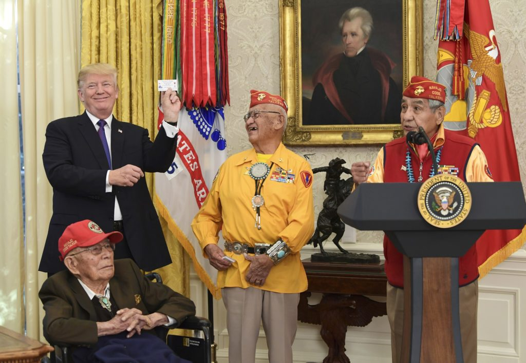 President Donald Trump, standing left, holds up the card of Navajo Code Talker Thomas Begay, center, during their meeting in the Oval Office of the White House in Washington, Monday, Nov. 27, 2017. Navajo Code Talkers Fleming Begaye Sr., seated, Peter MacDonald speaks at right. (AP Photo/Susan Walsh)