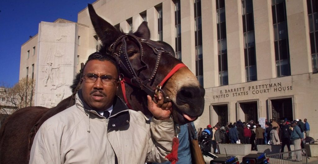 "National Black Farmer Association, Inc. President John Boyd, of Mecklenburg County, Va., and his mule ""Struggle"" take part in a demonstration by black farmers outside federal court in Washington Tuesday March 2, 1999 to express their opposition to a multimillion-dollar settlement of a discrimination lawsuit against the Agriculture Department. (AP Photo/Doug Mills)"