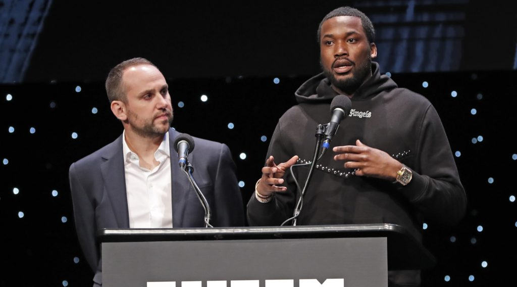 Philadelphia 76ers co-owner and Fanatics executive Michael Rubin, left, listens as recordng artist Meek Mill speaks at the launch of a partnership of sports, business and recording artists who hope to transform the American criminal justice system, Wednesday, Jan. 23, 2019, in New York. (AP Photo/Kathy Willens)
