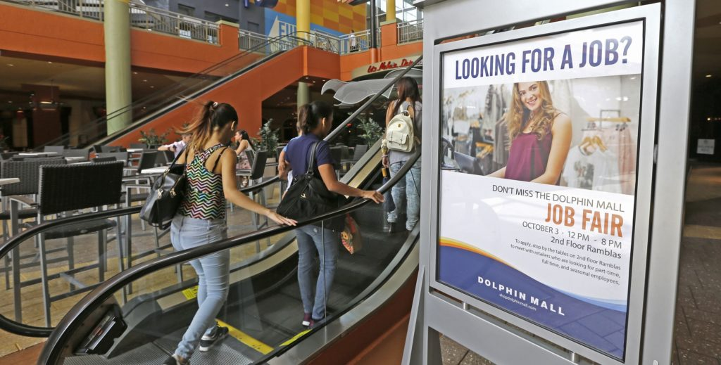 In this Tuesday, Oct. 3, 2017, photo, people head to at a job fair at Dolphin Mall in Sweetwater, Fla. The shopping center hosted a job fair in preparation for the approaching busy holiday retail season. On Thursday, Oct. 5, 2017, the Labor Department reports on the number of people who applied for unemployment benefits a week earlier. (AP Photo/Alan Diaz)