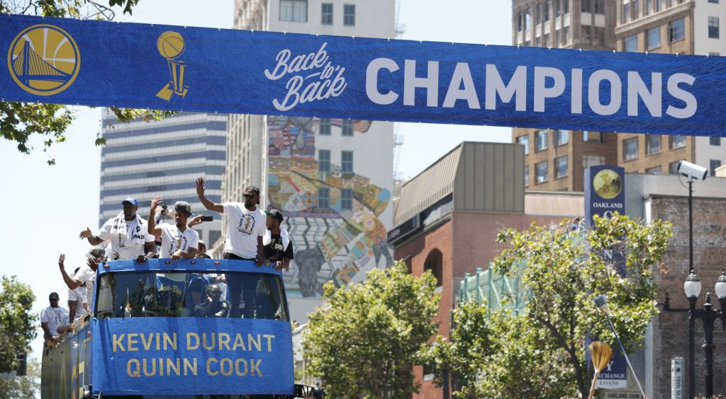 A champions banner is placed overhead as a bus carrying Golden State Warriors' Kevin Durant and Quinn Cook rides down the route during the team's NBA basketball championship parade, Tuesday, June 12, 2018, in Oakland, Calif. (AP Photo/Tony Avelar)