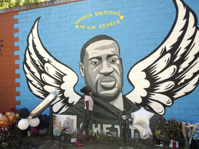 Nala Williams, 8, looks up at a mural honoring George Floyd in the Third Ward, Sunday, June 7, 2020, in Houston. Floyd, who grew up in the Third Ward, died after being restrained by Minneapolis Police officers on Memorial Day. (AP Photo/David J. Phillip